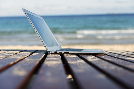 Laptop alone on empty oceanfront beach chair.